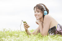 Side view of young woman listening to music through cell phone using headphones while lying on grass against clear sky
