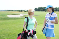 Popular : Smiling female golfers talking at golf course