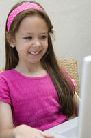 Smiling little girl using a laptop