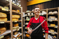 Smiling male salesperson holding knife in cheese store