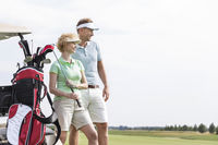 Popular : Smiling man and woman standing at golf course against clear sky