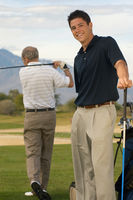 Popular : Smiling young man standing on golf course with older man