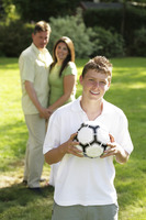 Teenage boy holding a soccer ball with his parents standing in the background