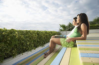 Popular : Teenage couple  16-17  sitting on wooden deck looking at view side view