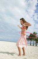 Popular : Teenage girl  16-17  playing with hoola hoop on beach