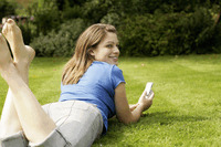 Teenage girl lying forward on the field playing with her mobile phone