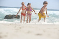 Three children  5-6 7-9 10-12  running on beach