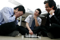 Three men playing chess in the office
