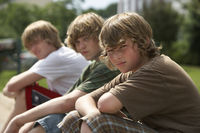 Popular : Three teenage brothers  13-17  sitting on street curb portrait