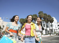Popular : Three teenage girls  16-17  carrying shopping bags walking on street