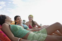 Popular : Three teenage girls  16-17  relaxing on sunloungers