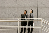 Two businessmen looking up