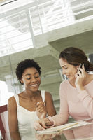 Two businesswomen in conference meeting one using mobile phone