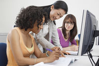 Two female students working with teacher in computer classroom