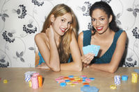 Two girls playing cards at table portrait
