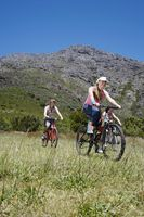 Popular : Two teenage girls and boy  16-17 years  biking mountain in background