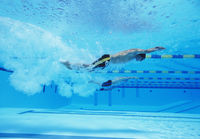 Underwater shot of three male athletes racing in swimming pool