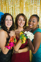 Popular : Well-dressed teenage girls showing corsages at school dance portrait