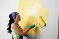 Woman applying yellow paint to interior wall