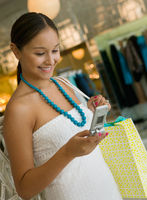 Woman checking cell phone while shopping in clothing store