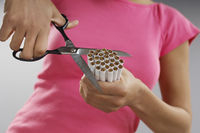 Woman cutting bundle of cigarettes close-up