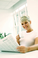 Popular : Woman holding a cup while reading newspaper
