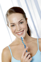 Woman holding a toothbrush smiling