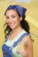 Woman holding paint roller portrait