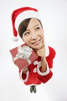 Woman in santa suit thinking while holding present