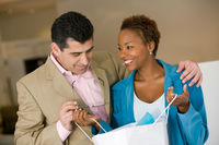 Woman in store showing man purchases in shopping bag front view