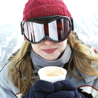 Woman in warm clothing holding a cup of hot drink