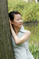 Woman leaning against the tree with her eyes closed
