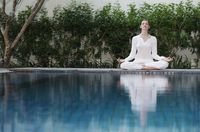 Woman meditating by the pool side