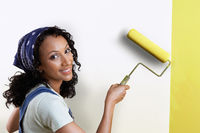 Woman painting wall yellow portrait
