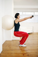 Woman pressing fitness ball against the wall while lifting dumbbells