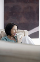 Woman sitting on the couch enjoying a cup of coffee