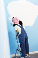 Woman standing on stepladder painting interior wall back view elevated view