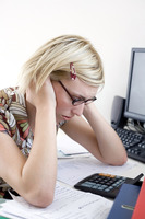 Woman stressed working at desk in a home office