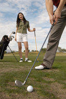 Popular : Woman watching man preparing to hit golf ball on golf course