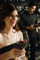 Woman with a glass of red wine  man selecting wine bottle in the background