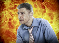 Worried businessman with fire in background