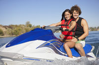Young couple riding jetski on lake portrait