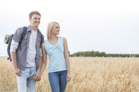 Young hiking couple holding hands while standing on field