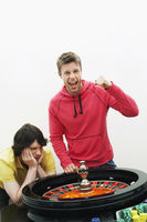Young man celebrating at roulette wheel while friend loses portrait