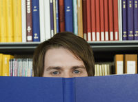 Young man peeking over opened book