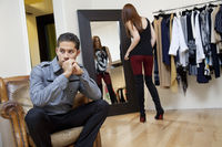 Young man sitting on armchair looking away while girlfriend looking herself in mirror