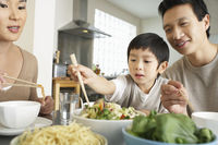 Young parents sitting at table watching son trying to use chopsticks