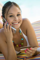 Young woman in bikini on deck chair by pool making credit card purchase on cell phone portrait