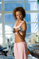 Popular : Young woman using dumbbell in gymnasium