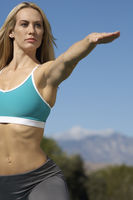 Young woman with arm extended exercising outdoors